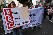 22 DECEMBER 2013 - BANGKOK, THAILAND: An anti-government protestor carries a sign critical of BBS news in Bangkok. Protestors are growing increasingly critical of foreign reporters who the protestors say support the elected government of Yingluck Shinawatra. Hundreds of thousands of Thais gathered in Bangkok Sunday in a series of protests against the caretaker government of Yingluck Shinawatra. The protests are a continuation of protests that started in early November and have caused the dissolution of the Pheu Thai led government of Yingluck Shinawatra. Protestors congregated at home of Yingluck and launched a series of motorcades that effectively gridlocked the city. Yingluck was not home when protestors picketed her home.     PHOTO BY JACK KURTZ