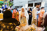"08 AUGUST 2013 - BANGKOK, THAILAND: A woman buys food at an outdoor market next to Haroon Mosque after Eid al-Fitr services. Eid al-Fitr is the ""festival of breaking of the fast,"" it's also called the Lesser Eid. It's an important religious holiday celebrated by Muslims worldwide that marks the end of Ramadan, the Islamic holy month of fasting. The religious Eid is a single day and Muslims are not permitted to fast that day. The holiday celebrates the conclusion of the 29 or 30 days of dawn-to-sunset fasting during the entire month of Ramadan. This is a day when Muslims around the world show a common goal of unity. The date for the start of any lunar Hijri month varies based on the observation of new moon by local religious authorities, so the exact day of celebration varies by locality.      PHOTO BY JACK KURTZ"