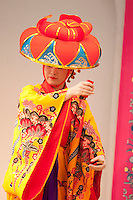 A woman dancer in traditional Okinawan (Ryukyu) kimono performs on stage at Ryukyu Mura on the main island of Okinawa.