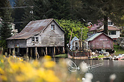 An old wooden home, boat and shed on the water in Petersburg, Alaska.