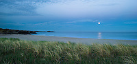 Sommernatt med fullmåne som er i ferd med å gå ned i havet over Brusand i Hå kommune, Rogaland, Jæren.
