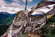 Bon inscription stone and prayer flags. Near the summit of Mt. Kongpo Bonri, Kongpo Region, Tibet.