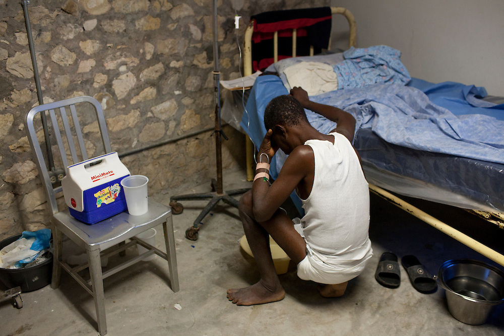 A man sick with cholera vomits next to his bed at the Hospital Albert Schweitzer on Saturday, October 30, 2010 in Deschapelles, Haiti.