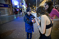 Amanda Anderson, a member of the the Derby Street Pastor team handing out 'spikeys' - anti-drink spiking devices - while on patrol in Derby city centre. Street Pastor was pioneered in London in January 2003 and Derby Street Pastors is a partnership of 25 local churches, Derbyshire Police, local council and various groups concerned with city centre street business and safety. Each Street Pastor team member works a minimum of one night a month, usually from 10pm to around 4am.