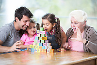 Cute girl blowing alphabet blocks while family looking at it in house