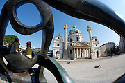 "Karlsplatz. The baroque Karlskirche built by Johann Bernhard Fischer von Erlach 1716-37 seen through the sculpture ""Hill Arches"" presented to the City of Vienna by Henry Moore."