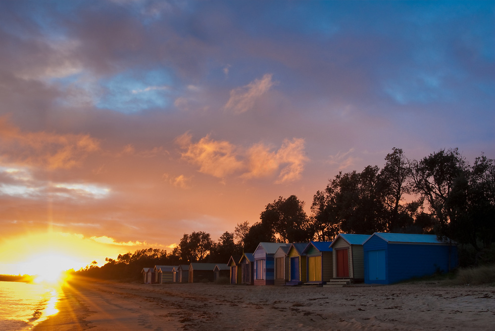 Colourfully painted beach huts at sunrise on Dromana Beach