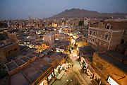 Lights illuminate the narrow streets of the souk in the old city of Sanaa, Yemen at dusk.