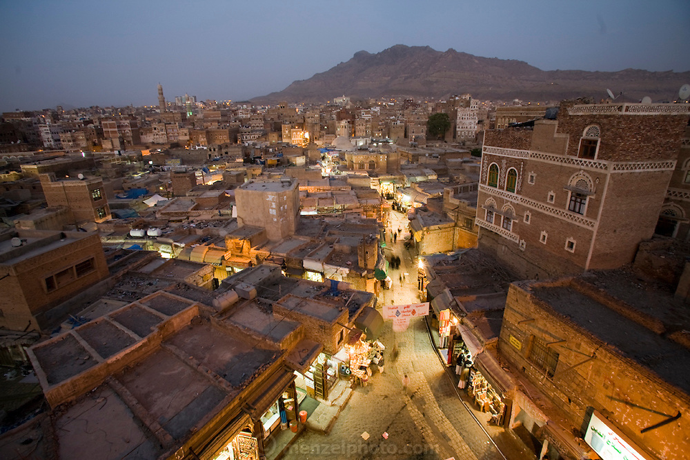 Lights illuminate the narrow streets of the souk in the old city of Sanaa, Yemen at dusk.
