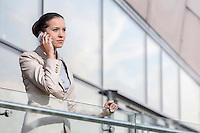 Confident young businesswoman using smart phone at office railing