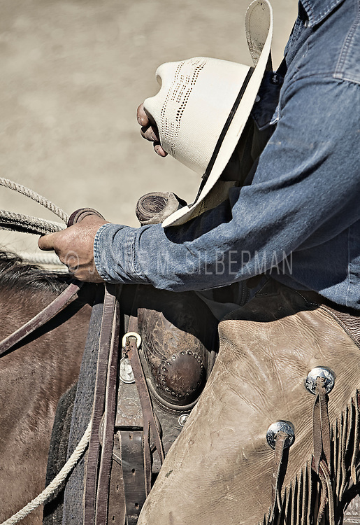 Detail of a cowboy, hat in hand, astride his horse, pausing for the singing of the national anthem before the start of the rodeo.