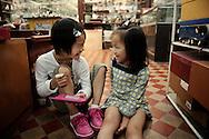 Anna lei (a droite, 5 ans) et  Meilynn (a gauche 9 ans) jouent ensemble dans un magasin de souvenirs pour touristes de l'ile de Shamian a Canton. Il y a une semaine les deux enfants ne se connaisaient pas. Elles sont desormais soeurs. Elles ont toutes deux ete adoptees par Chad et terri de l'Indiana. Annalei a ete adopte il y a quatre ans et a fait le voyage en Chine avec ses parents pour chercher Meylinn. Meilynn ne parle pas l'anglais, mais cela ne l'empeche pas de jouer avec sa nouvelle petite soeur.