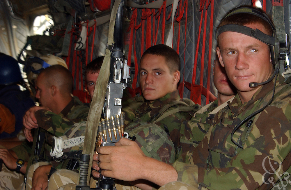 """British Royal Marines of 45 Commando ride inside a Chinook helicopter during an """"eagle vehicle check point"""" (VCP) mission as part of the ongoing Operation Buzzard July 8, 2002 in southeastern Afghanistan. During VCPs, small groups of marines are dropped quickly by helicopters to search random vehicles on dirt roads and trails near the Pakistan-Afghanistan border to deny al Qaeda and Taliban fighters freedom of movement across the region."""