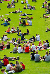 People sitting on lawn at Princes Street Gardens in warm summer weather in Edinburgh, Scotland UK