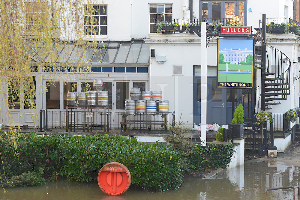© Licensed to London News Pictures. 03/01/2014. Guildford, UK . A pub raises its beer barrels from the basement and uses tables to store them above the flood line. Guilford town centre River Wey bursting it's banks in Surrey today 3rd January 2013. Floods an heavy rain are continuing to effect travel and people across the country today. Photo credit : Stephen Simpson/LNP