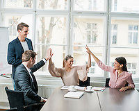 Young business team doing high five at conference table