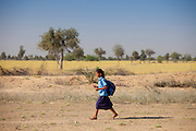 Young Indian girl in school uniform walking barefoot to her school near Rohet in Rajasthan, Northern India