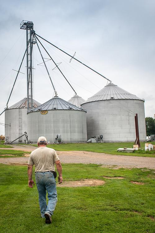 A farmer walking towards a row of silos