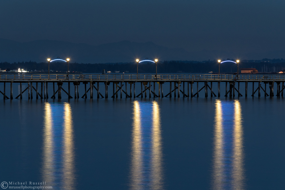 Lights on the White Rock Pier reflected in the water of Boundary Bay.  Photographed in White Rock, British Columbia, Canada