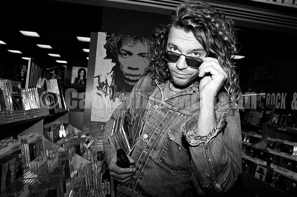 NEW YORK - OCTOBER 1993:  Australian singer songwriter Michael Hutchence (1960-1997) of the rock band INXS, poses for a photo in front of a poster of Jimi Hendrix while shopping for CDs at Tower Records in October 1993 in New York City, New York. (Photo by Catherine McGann)Copyright 2010 Catherine McGann