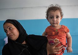 """© Licensed to Alison Baskerville. 14/07/2014. Gaza.   """"When I hold my daughter in my arms I forget the whole world.""""  Comments Ablu Abu Hamillah (38) as she joins over 600 in a UN School within Gaza city.  Many have fled the north left with limited supplies.  With no sign of the crisis ending the school is now concerned that they will run out of water and supplies.  """"I don't know how much longer we will be able to go on in this situation.""""  Commented Abdil Sawan, the UN representative within the school.   Photo credit : Alison Baskerville/LNP"""