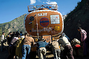 A group of men is pushing a truck on slippery and muddy soil common of the Leh-Manali Highway.