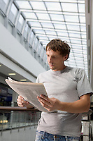 Young man stands reading newspaper in new shopping centre Voronezh