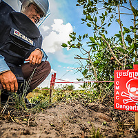 Cambodia has been dealing with the insurmountable task leftover from decades of war and its legacy, unexploded ordnance or UXOs. Estimates range from 3 to 9 million unexploded bombs that are still just beneath the surface throughout the region. These bombs are left over from air strikes, artillery fire, mortar shells, rockets, grenades, anti-personnel and anti-vehicle land mines are indiscriminate weapons and do not expire, often killing or injuring between 100 to 200 people in Cambodia a year. With little resource, the countries' people and Non Governmental Organizations (NGOs) are still facing over a hundred years being exposed to this deadly issue while walking and cultivating their land in fear.<br /> <br /> Cambodian Mine Action Centre (CMAC) worker clad in protective gear donated by the Japanese inspects a unexploded shell in the dirt where his team searches for land mines and unexploded ordnance using a metal detectors to sweep a field in the Cambodian countryside province of Kampong Thom. Jan. 2013.