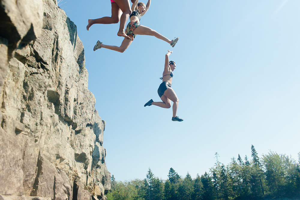 Young woman jummping into quarry.
