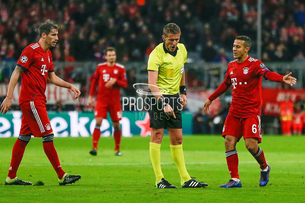 Referee Daniele Orsato signals for a free kick, Bayern Munich midfielder Thiago Alcantara (6) protests, during the Champions League match between Bayern Munich and Liverpool at the Allianz Arena, Munich, Germany, on 13 March 2019.