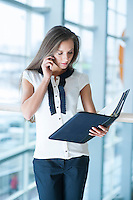 Businesswoman on mobile phone reading from folder