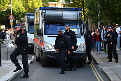 © Licensed to London News Pictures. 16/06/2017. London, UK. Large numbers of riot police make their way towards Grenfell Tower. A demonstration and march by residents and campaigners arrives at Grenfell Tower in west London following a fire at the Grenfell tower block in west London earlier this week. The blaze engulfed the 27-storey building killing 12 - with 34 people still in hospital, 18 of whom are in critical condition. The fire brigade say that they don't expect to find anyone else alive. Photo credit: Ben Cawthra/LNP