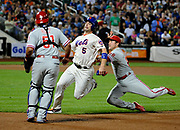 Philadelphia Phillies second baseman Chase Utley leaps to tag out New York Mets David Wright in a run down between first and second base as catcher Carlos Ruiz readies for backup during a baseball game, Aug. 30, 2014, in New York. <br /> (AP Photo/Kathy Kmonicek)