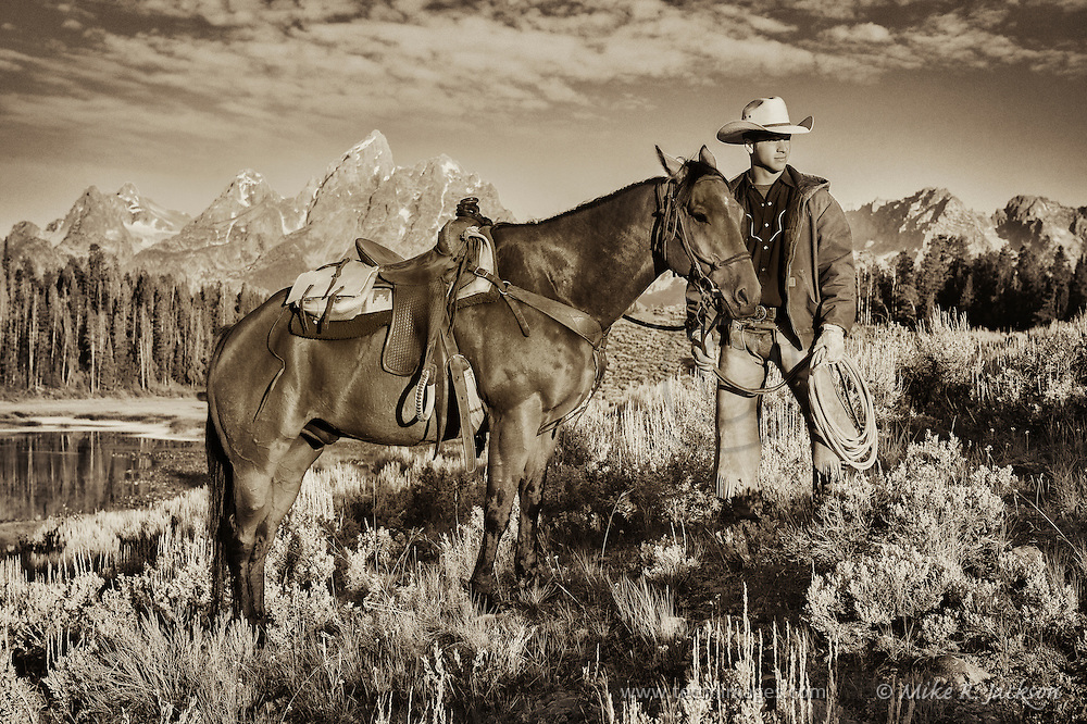 A Wrangler pauses with his horse with the majestic Grand Teton mountain range in the background.