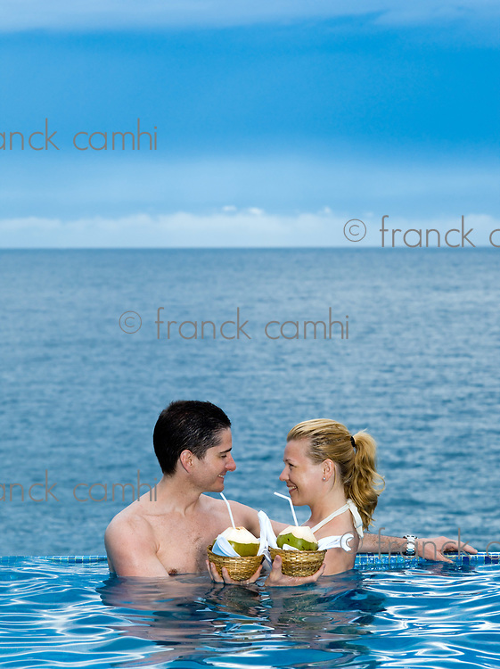 beautiful caucasian couple enjoying their vacation in a swimming pool by the seaside drinking coconut milk
