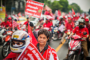 """10 DECEMBER 2012 - BANGKOK, THAILAND:   The Red Shirt motorcade in Bangkok Monday. The Thai government announced on Monday, which is Constitution Day in Thailand, that will speed up its campaign to write a new charter. December 10 marks passage of the first permanent constitution in 1932 and Thailand's transition from an absolute monarchy to a constitutional monarchy. Several thousand """"Red Shirts,"""" supporters of ousted and exiled Prime Minister Thaksin Shinawatra, motorcaded through the city, stopping at government offices and the offices of the Pheu Thai ruling party to present demands for a new charter.       PHOTO BY JACK KURTZ"""