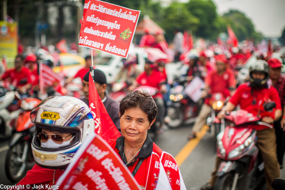 "10 DECEMBER 2012 - BANGKOK, THAILAND:   The Red Shirt motorcade in Bangkok Monday. The Thai government announced on Monday, which is Constitution Day in Thailand, that will speed up its campaign to write a new charter. December 10 marks passage of the first permanent constitution in 1932 and Thailand's transition from an absolute monarchy to a constitutional monarchy. Several thousand ""Red Shirts,"" supporters of ousted and exiled Prime Minister Thaksin Shinawatra, motorcaded through the city, stopping at government offices and the offices of the Pheu Thai ruling party to present demands for a new charter.       PHOTO BY JACK KURTZ"