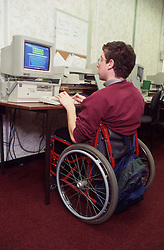 Man with disability; who is wheelchair user; using computer in office,