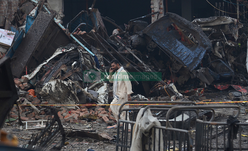August 8, 2017 - Lahore, Punjab, Pakistan - Pakistani security officials investigate the site following an overnight bomb explosion placed inside a truck in Lahore. A truck bomb injured at least 34 people and 2 dead late on August 7 in Pakistan, officials said, in the latest bombing to rattle the eastern city of Lahore. 'The explosive material was planted inside a truck which was loaded with fruit. (Credit Image: © Rana Sajid Hussain/Pacific Press via ZUMA Wire)