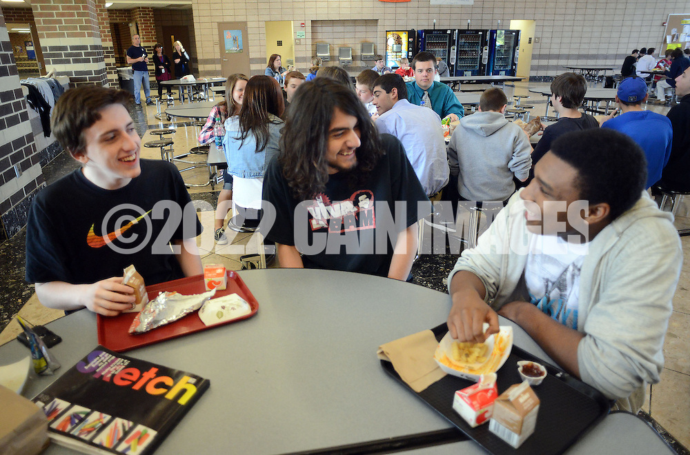 WARRINGTON, PA - APRIL 28:  From left, Tom Krebs, 15 of Warrington, Pennsylvania, Caleb Cordova, 15 of Chalfont, Pennsylvania and Ameer Dunn, 16 of Warrington, Pennsylvania chat as they have lunch at Central Bucks South April 28 2014 in Warrington, Pennsylvania. Aramark, Central Bucks' food service provider, has asked the district to consider opting out of the National School Lunch Program on the high school level. The district would lose some federal funding if it does so, but it stands to lose much more in revenue because of changes coming next year regarding snacks and a la carte items sold to students.  (Photo by William Thomas Cain/Cain Images)