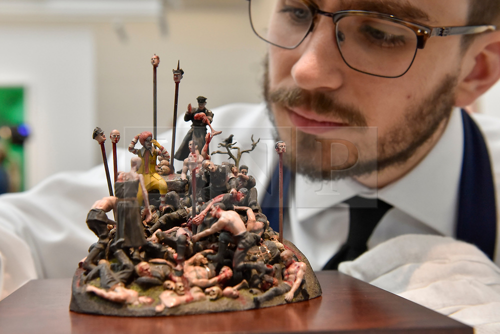 """© Licensed to London News Pictures. 12/10/2017. London, UK.  A technician inspects """"My Cat Went to See Hell and All I Got Was This Lousy Souvenir"""", 2007-13, by Jake & Dinos Chapman (Est. GBP10-15k) at a preview of artworks for the """"Art for Grenfell"""" auction taking place at Sotheby's, New Bond Street, on 16 October.  Leading contemporary artists have agreed to donate works to the auction, the proceeds of which will be divided equally amongst the 158 surviving families of the Grenfell Tower fire by the Rugby Portobello Trust charity. Photo credit : Stephen Chung/LNP"""