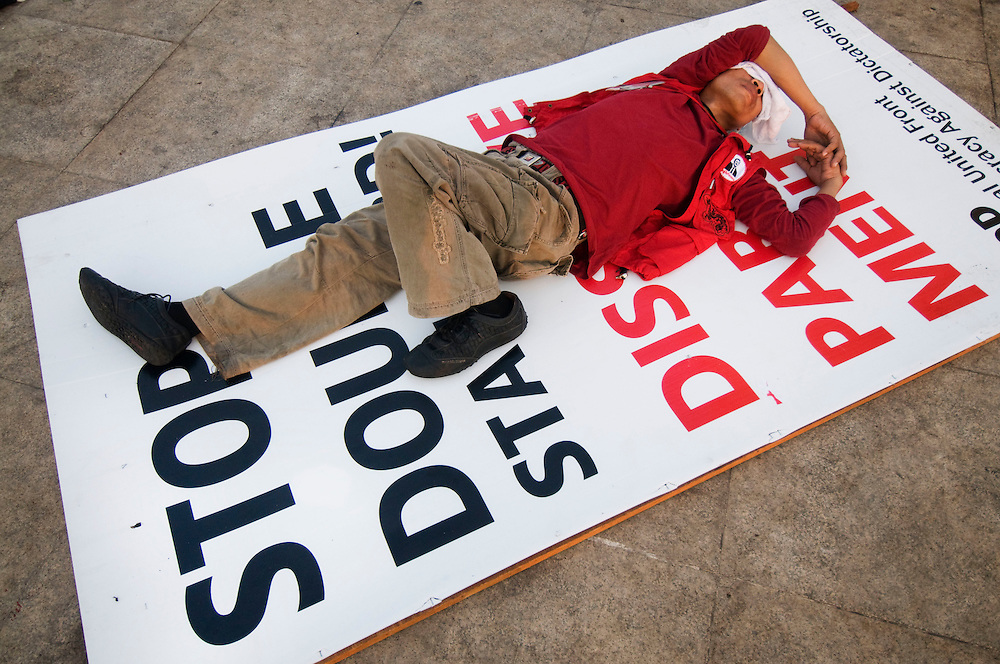 A Red Shirt anti government protestor sleeps under the Democracy Monument in Bangkok, Thailand on Sunday, April 11, 2010