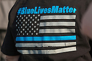 "Goshen, New York - A woman wears a ""Blue Lives Matter"" shirt at the Orange County Law Enforcement Officer Memorial Service on May 8, 2015, at the entrance of the Orange County Courthouse. The memorial service honors the memory of the members of the Orange County law enforcement community that died in the line of duty. The service also pays tribute the families and loved ones left behind for their courage, dignity and perseverance."