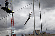 Student Ashleigh Blair swings at Trapeze School New York during the June 4th morning class. The two hour beginner session taught the nine students in attendance the basics of flying trapeze -- including knee hangs and backwards somersaults -- in their facility on the roof of Pier 40...CREDIT: Daniella Zalcman for The Wall Street Journal.SLUG: NYMETROMONEY_Trapeze