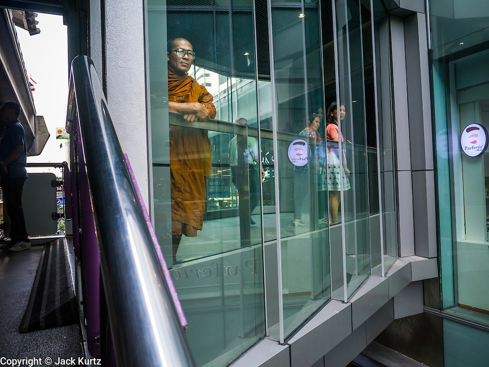 16 JANUARY 2013 - BANGKOK, THAILAND:   A Buddhist monk stands at the top of the stairs of Sala Daeng BTS Skytrain stop on Silom Road in Bangkok.   PHOTO BY JACK KURTZ