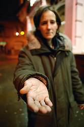 Homeless woman holding her hand out and begging in the inner city streets,