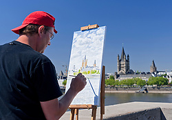 Man painting churches and cityscape of Cologne in Germany