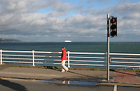 Wintertime at the Seafront at DunLaoghaire in Dublin Ireland, woman walking past the pedestrian crossing