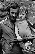 Beirut, Lebanon Aug  1985. Bir el Abed,  southern suburb. A father and his son posing with the father's assault riffle (AK-47) for the photographer. ©Herve Merliac