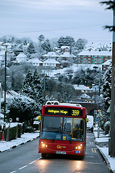 © Licensed to London News Pictures. 17/01/2016. Croydon, UK. A bus climbs up Sanderstead Hill surrounded by snow in Croydon, South London. . Photo credit : Ian Schofield/LNP